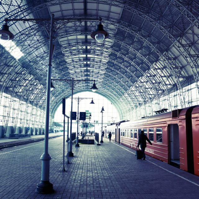 Covered old railway station with train and silhouettes of people